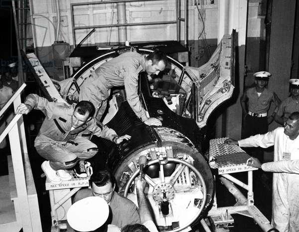GEMINI IV: ASTRONAUTS, 1965 Astronauts Edward White and James McDivitt examining their capsule after landing, 1965.
