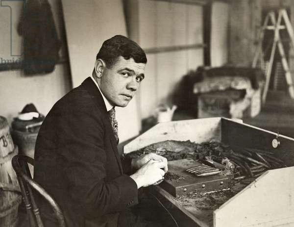 GEORGE H. RUTH (1895-1948) Known as Babe Ruth. American professional baseball player. Photographed rolling cigars, c.1919.