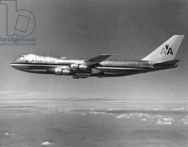 AMERICAN AIRLINES PLANE A Boeing 747 passenger plane operated by American Airlines in flight over a mountain range. Photograph, late 20th century.