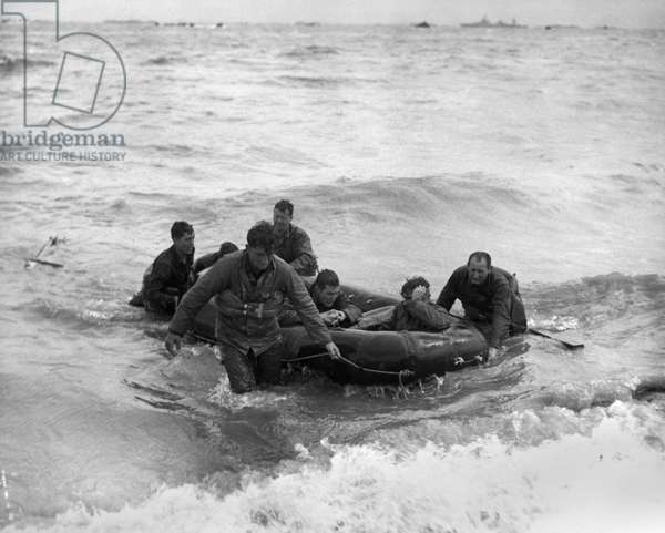 WORLD WAR II: NORMANDY American survivors of a sunken LCVP landing craft come safely ashore during the D-Day invasion of Omaha Beach, Normandy, France, 6 June 1944.
