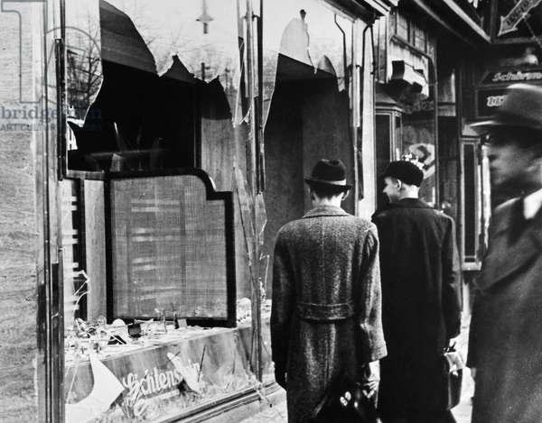 KRISTALLNACHT, 1938 Pedestrians in Berlin, Germany, observing the smashed windows of a Jewish shop following the Kristallnacht pogrom, 10 November 1938.