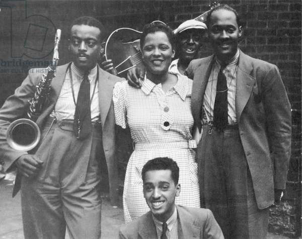 BILLIE HOLIDAY (1915-1959) American singer. In a Harlem alley with Ben Webster (left) and other musicians. Photographed in 1935.