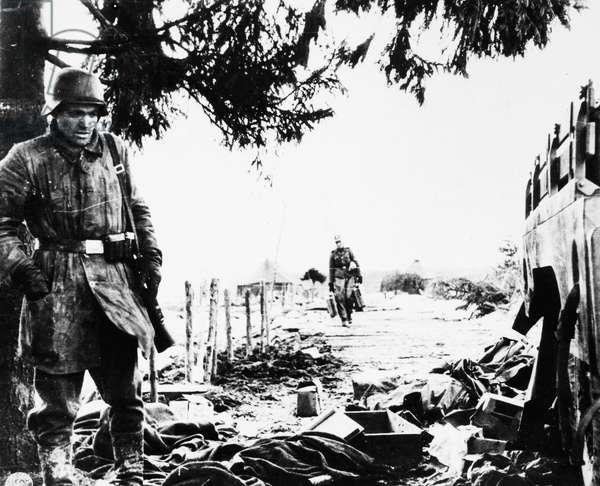 WORLD WAR II: BELGIUM, 1944 A German soldier examines litter left behind by American soldiers in territory taken by the Germans in the Belgian breakthrough, December 1944.