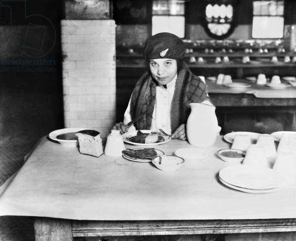 ELLIS ISLAND: DINING ROOM A young immigrant woman eating a meal in the dining hall in the Kitchen and Laundry building at Ellis Island, New York City. Photograph, early 20th century.