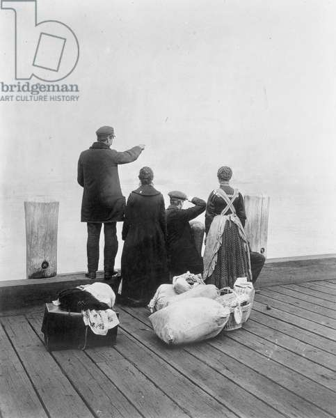 IMMIGRANT FAMILY, 1912 Immigrants on the dock at Ellis Island in New York Harbor, 1912.