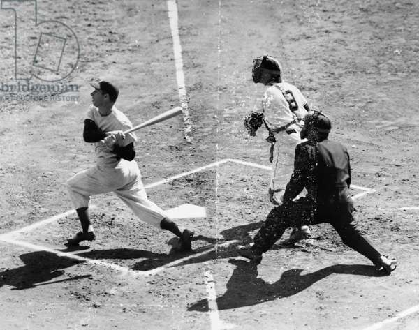 JOE DIMAGGIO (1914-1999) American baseball player. As a member of the New York Yankees, fouling off a pitch while batting against the New York Giants in Game 4 of the 1951 World Series at the Polo Grounds in New York City, 8 October 1951. Watching at right are Giants catcher Wes Westrum and home plate umpire Al Barlick.
