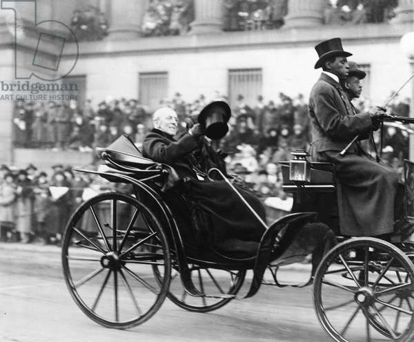 WOODROW WILSON (1856-1924) 28th President of the United States. President Wilson waves to the crowd from a carriage during an Armistice Day procession. Photographed 11 November 1921.