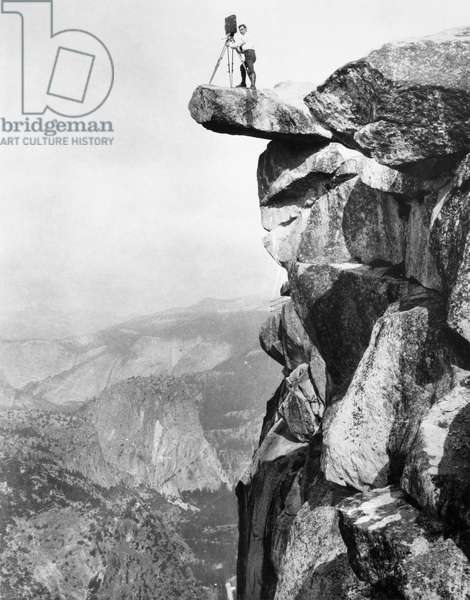 YOSEMITE: GLACIER POINT William Henry Jackson photographing from a rock ledge of Glacier Point in Yosemite National Park. Photograph, c.1900.