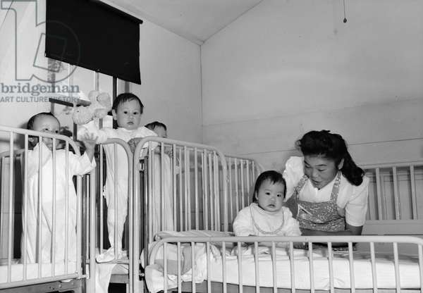 JAPANESE INTERNMENT, 1943 Nurse at an orphanage at the Manzanar Relocation Center for Japanese Americans near Owens Valley, California. Photograph by Ansel Adams, 1943.