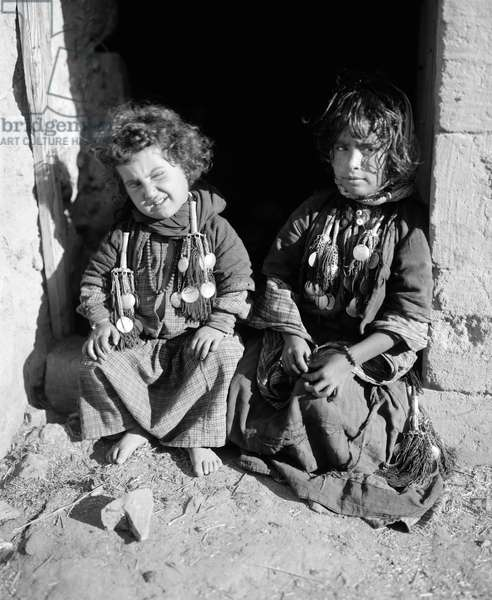 BEDOUIN CHILDREN Two Bedouin children seated in a doorway in the Middle East. Photograph, early 20th century.