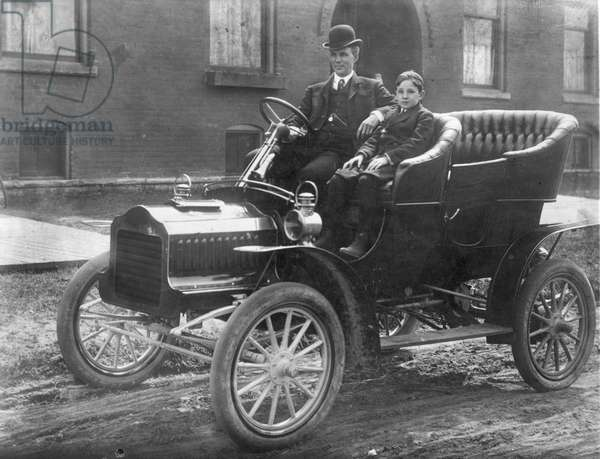 HENRY FORD (1863-1947) with his son Edsel in a 1905 Model F Ford in front of their home on Hendrie Avenue in Detroit.