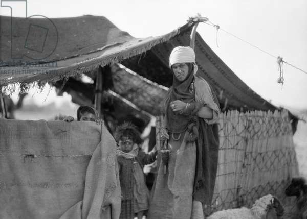IRAQ: BEDOUIN HOME, c.1932 A Bedouin woman with two children at their tent near Nineveh, Iraq. Photograph, c.1932.