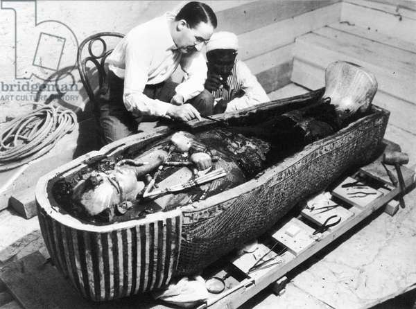 HOWARD CARTER (1873-1939) English archaeologist. Carter and an Egyptian assistant examining the sarcophagus of King Tutankhamen, found during the excavation of his tomb in the Valley of the Kings, Egypt, October 1925. Photographed by Harry Burton.