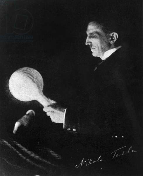 NIKOLA TESLA (1856-1943) American electrician and inventor. Born in Croatia, of Serbian parents. Tesla holding an electric light. Photograph, c.1900.