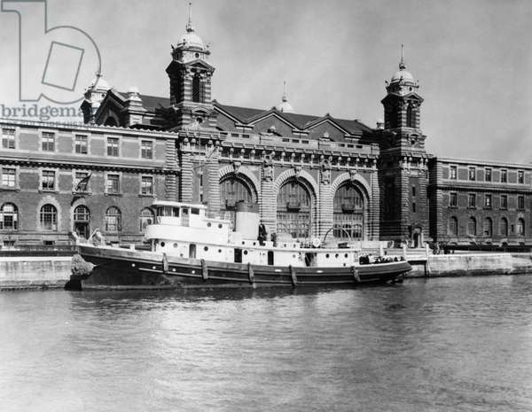 ELLIS ISLAND, 1930s The main building and one of the boats used for taking immigrants to lower Manhattan. Photograph, c.1932.