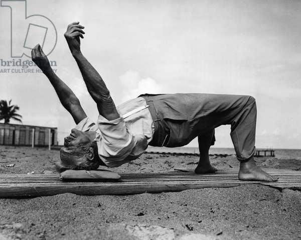 BERNARR MACFADDEN (1868-1955). American physical culturist. Photographed in a 'wrestler's bridge' stretching pose at his home in Miami Beach, Florida, at the age of 75, February 1943.