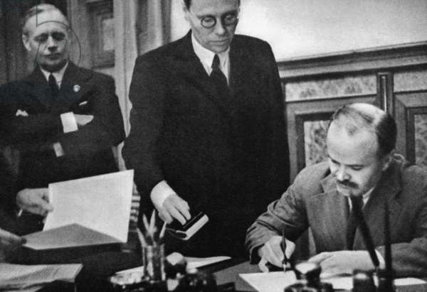 NAZI-SOVIET PACT, 1939 Soviet Foreign Minister Vyacheslav Molotov signing the Nazi-Soviet Non-Aggression Pact, 23 August 1939, in Moscow, Russia, at the start of World War II. Another singnatory, German Minister of Foreign Affairs Joachim von Ribbentrop (far left), looks on.