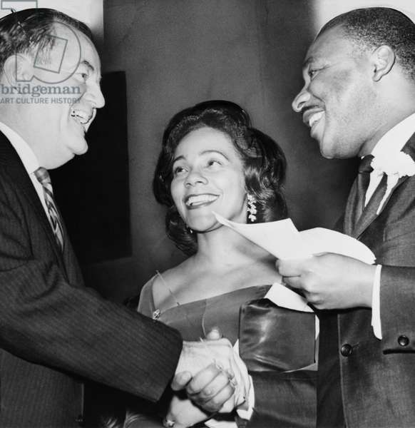 HUMPHREY AND KINGS, 1964 Vice President-elect Hubert Humphrey shaking hands with Dr. Martin Luther King, Jr., as Coretta Scott King looks on, at a rally at the 369th Regiment Armory in Harlem, New York City. Photograph by Orlando Fernandez, December 1964.