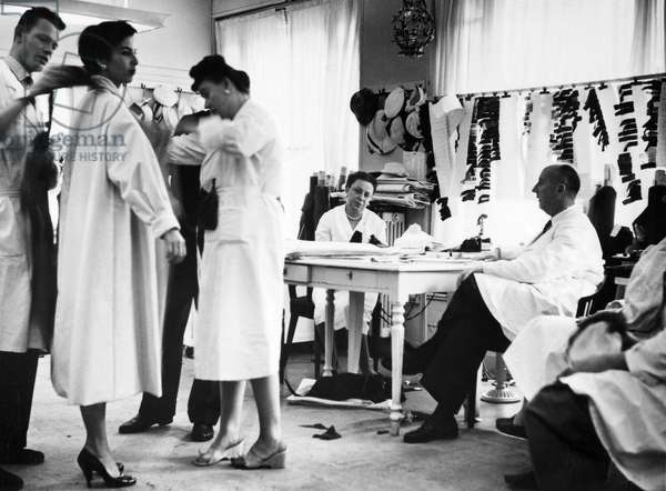 CHRISTIAN DIOR (1905-1957) French fashion designer. Dior in a studio, supervising the draping of a model, c.1950.