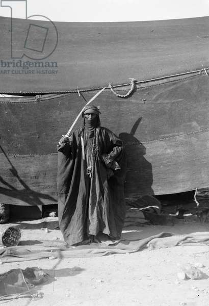 BEDOUIN MAN, c.1910 A cloaked Bedouin man with a sword. Photograph, c.1910.