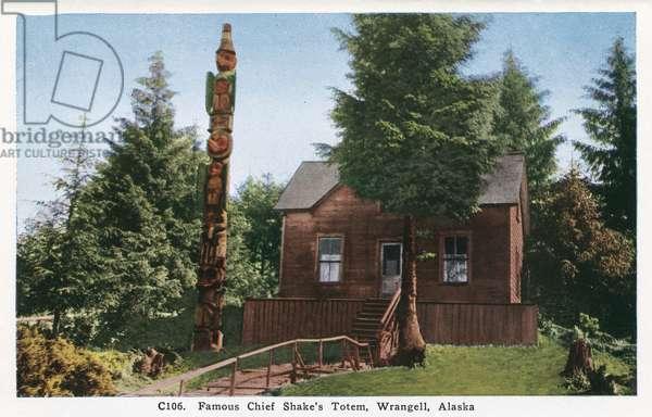 ALASKA: TLINGIT HOUSE Totem pole and house of the Tlingit Chief Shakes, in Wrangell, Alaska. Postcard, American, c.1930.