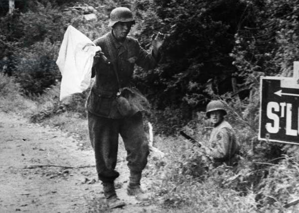 WWII: GERMAN SOLDIERS A German soldier carrying a white flag surrenders to American troops near Saint-Lo, France, c.1944.