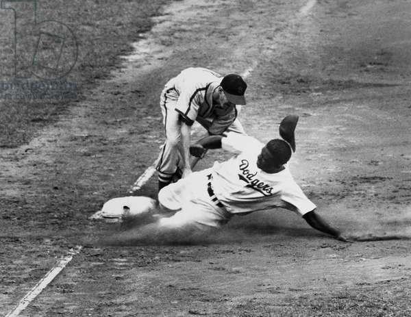 JACKIE ROBINSON (1919-1972) John Roosevelt Robinson, known as Jackie. American baseball player. As a member of the Brooklyn Dodgers, being tagged out at third base by shortstop Marty Marion of the St. Louis Cardinals during a game at Ebbets Field, Brooklyn, New York, 23 August 1949.