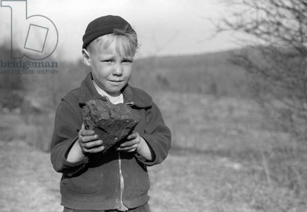 MINER STRIKE, 1939 A miner's son holding coal salvaged from a slag pile during a coal strike in Kempton, West Virginia. Photograph by John Vachon, May 1939.