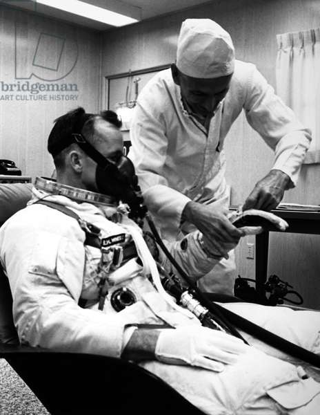 EDWARD WHITE (1930-1967) Astronaut Edward White is suited up for the Gemini IV mission by NASA suit technician, Joe Schmitt, on the morning of the launch, 3 June 1965.