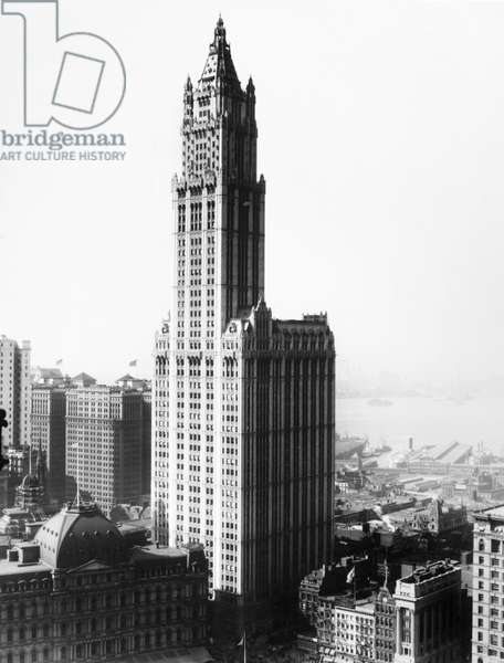 WOOLWORTH BUILDING, c.1935 The Woolworth Building, completed in 1913, in lower Manhattan. Hudson River piers can be seen in the background.