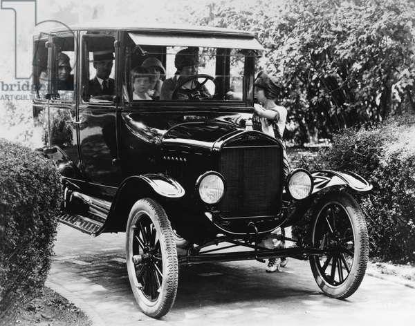 FORD SEDAN, 1923 A family driving a Ford sedan. Photograph, 1923.