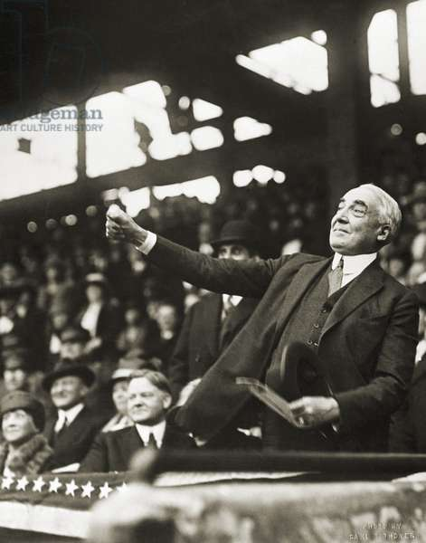 WARREN G. HARDING (1865-1929). 29th President of the United States. President Harding throwing out the first ball at the beginning of the major league baseball season, 1921. Secretary of Commerce Herbert Hoover is seated left.