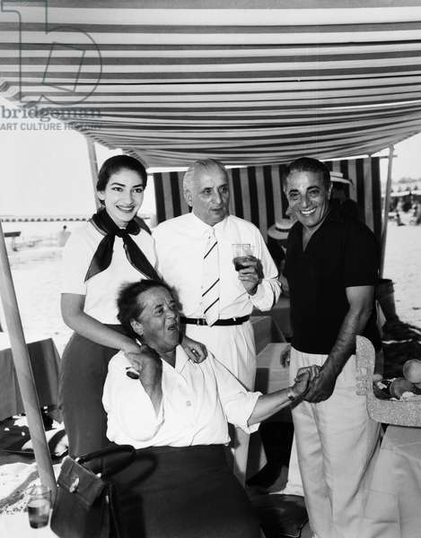 MARIA CALLAS (1923-1977) American operatic soprano. Callas (left) with her husband, Giovanni Battista Meneghini (center), shipping magnate Aristotle Onassis (right), and columnist Elsa Maxwell (seated) at a beach party given by Italian Countess Anna Castebarco in Venice, September 1957.