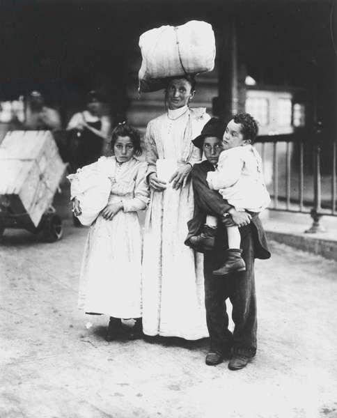 ELLIS ISLAND, c.1910 An Italian mother with her children at Ellis Island, c.1910.