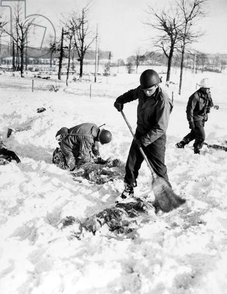 MALMEDY MASSACRE, 1944 American soldiers recovering the bodies of their comrades in a snow-covered field after they were massacred by German Waffen-SS soldiers near Malmedy, Belgium, during World War II, December 1944.