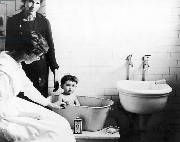 IMMIGRANTS: ELLIS ISLAND Social worker Lillian Wheeler giving an immigrant child a bath at Ellis Island under the eyes of his mother, c.1922.