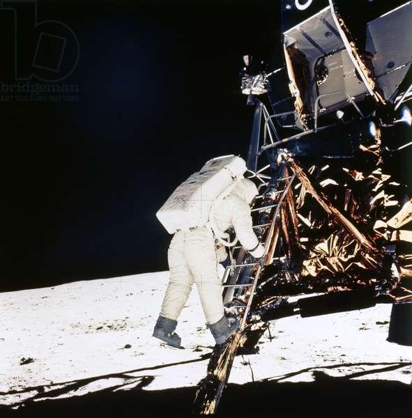 APOLLO 11 LANDING, 1969 Astronaut Edwin 'Buzz' Aldrin descending from the Apollo 11 lunar module on the surface of moon. Photograph, 1969.