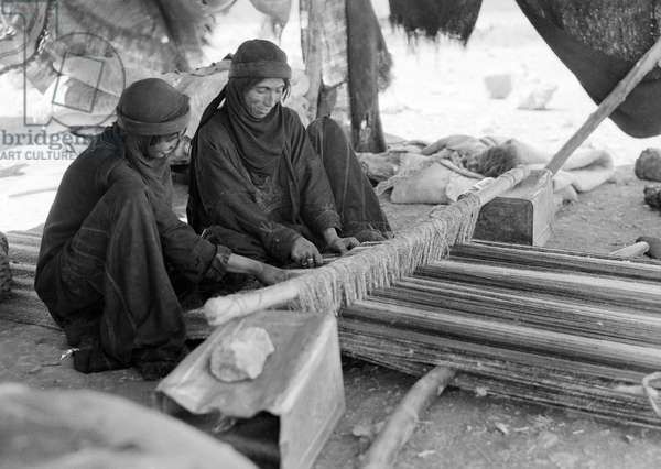 BEDOUIN WOMEN, c.1943 Two Bedouin women weaving on a loom in the Middle East, while a child sleeps on a blanket. Photograph, c.1943.