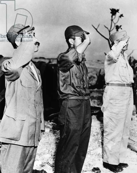 WWII: JAPAN, 1945 A Japanese officer saluting the American flag on Marcus Island, Japan. Photograph, 1945.
