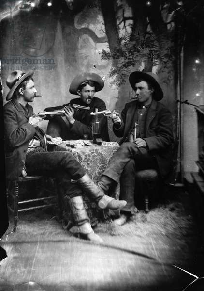 CARD PLAYERS, c.1870 Three gunslingers in the American West playing cards. Tintype, 19th century.