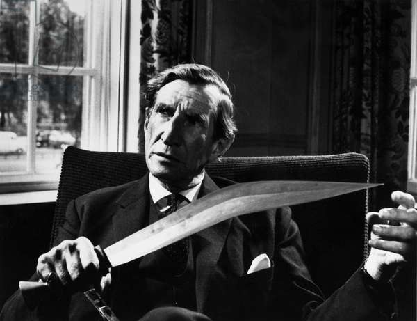 WILFRED THESIGER (1910-2003) British explorer. Photographed at the London Travelers Club, with a sword acquired during his travels in Africa, c.1970.