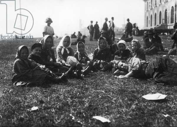 ELLIS ISLAND, 1920 A group of European immigrant children waiting on a lawn at Ellis Island, 24 September 1920.