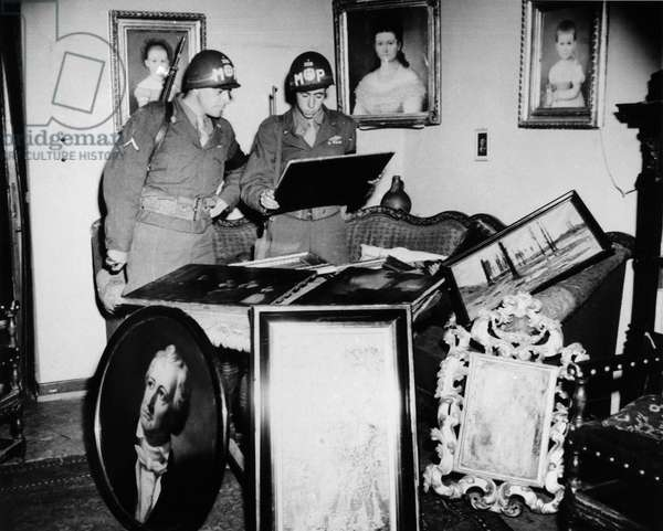 WORLD WAR II: STOLEN ART American military policement Matt Carlson and Sy Herold, look over a painting by Anthony Van Dyke that had belonged to Lady Nancy Astor and was recovered with other works of art at the home of Nazi leader Rudolph Reppert in Rematen, Germany. Photograph, July 1945.