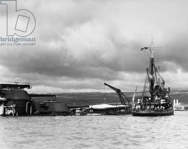 WWII: PEARL HARBOR, 1941 The USS Widgeon alongside the stern of the sunken USS Arizona, after the Japanese air attack on Pearl Harbor. Photograph, December 1941.