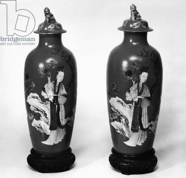 CHINA: PORCELAIN VASES A pair of porcelain sleeve vases with covers, each featuring an identical depiction of a woman carrying a flower in a vase. Ch'ien Lung period, Ching Dynasty, 1736-1796.