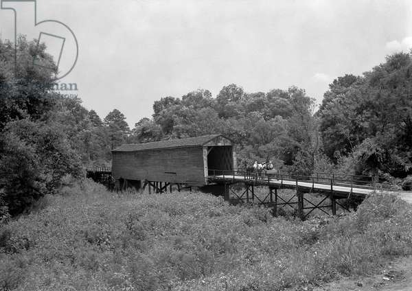 COVERED BRIDGE, 1936 A horse and carriage traveling across a covered bridge, near Eatonton, Georgia. Photograph by Carl Mydans, June 1936.