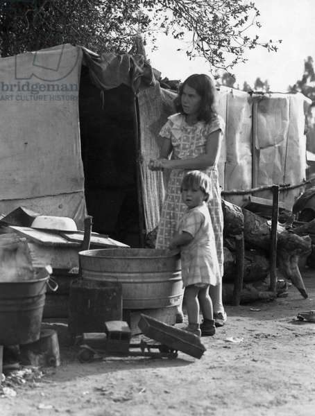 Mother and child using a wash basin in a rehabilitation camp for migrant workers and families in California, March 1935 (b/w photo)