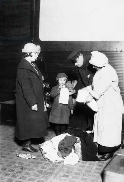 ELLIS ISLAND, 1921 A matron of the Health Department and a policeman examining incoming immigrants at the immigration station in New York Harbor, 17 March 1921.