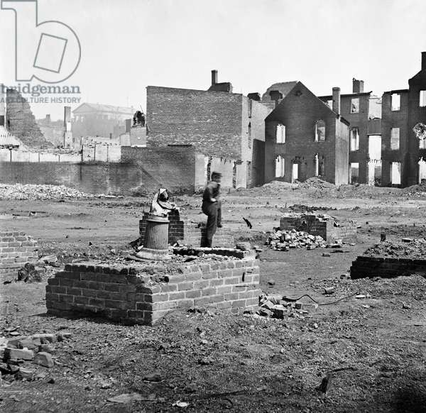 CIVIL WAR: RICHMOND, 1865 A Confederate soldier standing amongst the ruins in the burned district of Richmond, Virginia following the American Civil War. Photograph, 1865.