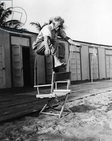 BERNARR MACFADDEN (1868-1955). American physical culturist. Jumping over a chair at his home in Miami Beach, Florida, at the age of 75. Photograph, February 1943.